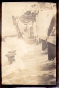 a photograph by francis davies aboard rrs william scoresby with unidentified but brave crew member hanging onto the deck, 1929
